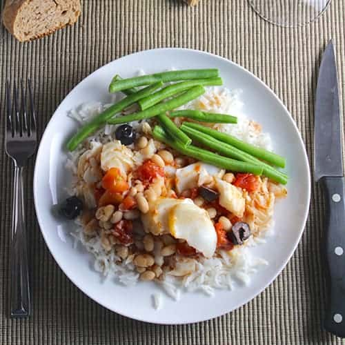 cod and beans served on a plate over rice, with a side of green beans.