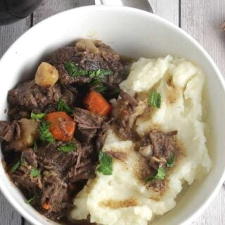 bowl of beef stew with mashed potatoes on the side.