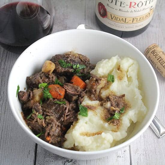 bowl of beef stew with side of mashed potatoes, served with a red wine.