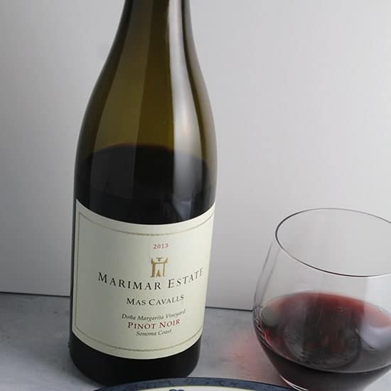 A glass of Marimar Estate Pinot Noir next to the bottle.