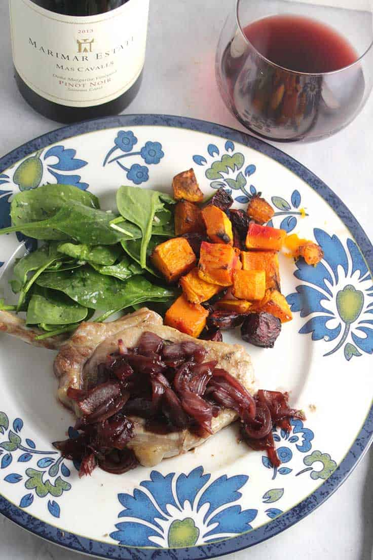 pork chop topped with pomegranate sauce, on a plate with vegetables, along with a glass of red wine.