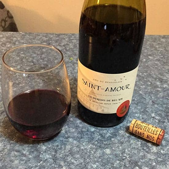 open bottle of Saint-Amour Cru Du Beaujolais with a glass of the red wine beside it.