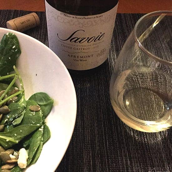 bottle of Savoie white wine with a glass on one side, spinach salad on the other side.