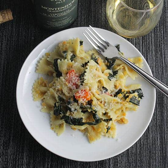 tuscan kale pasta on a plate with a glass of white wine on the side.