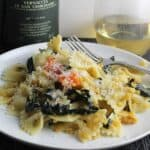 closeup of tuscan kale pasta on a plate with Vernaccia white wine in background.