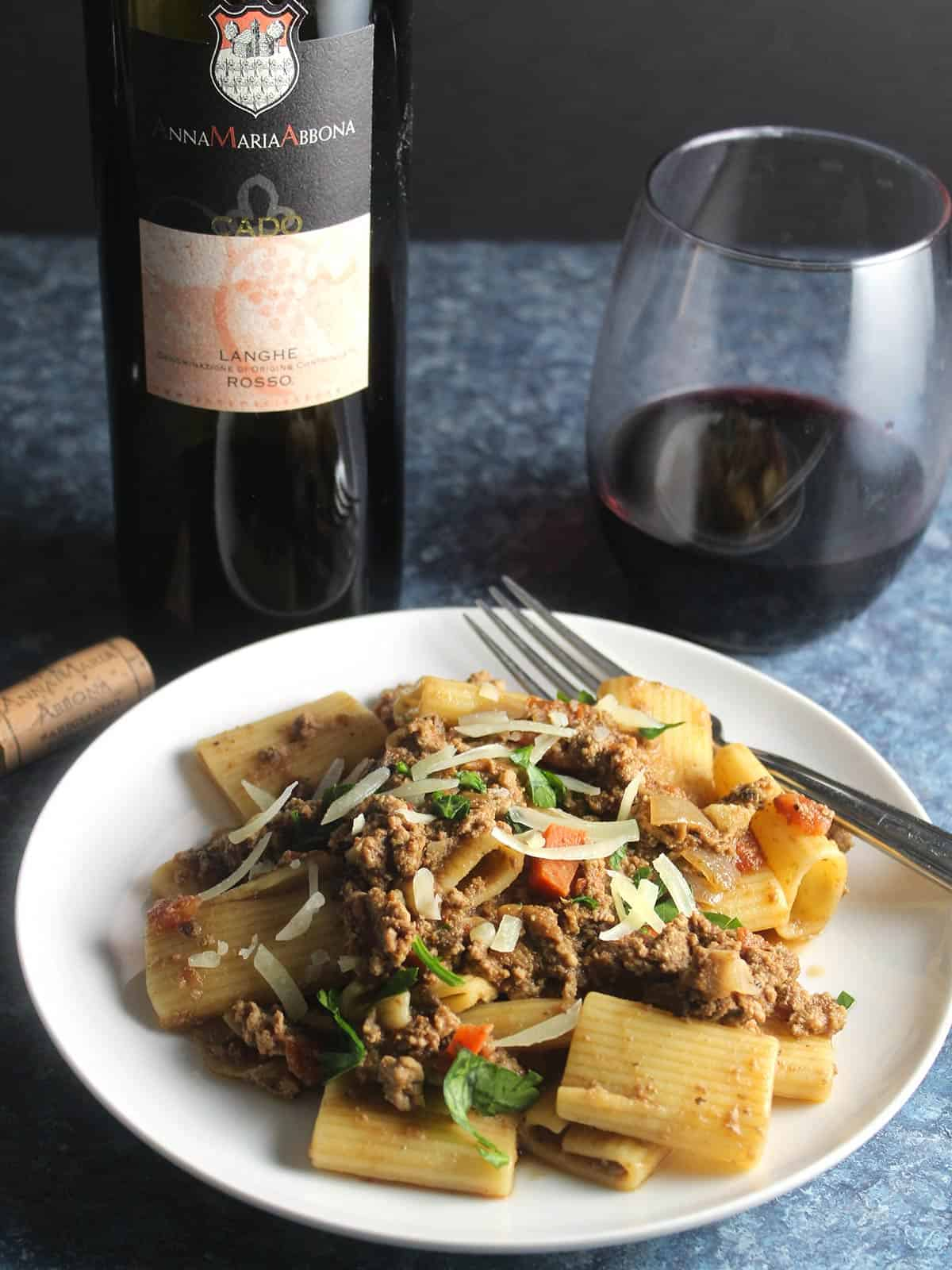 bolognese pasta served with red wine.