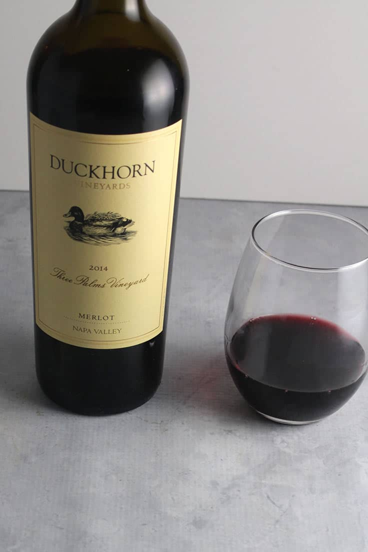 bottle of 2014 Duckhorn Three Palms Vineyard Napa Merlot with a glass of the wine next to the bottle.