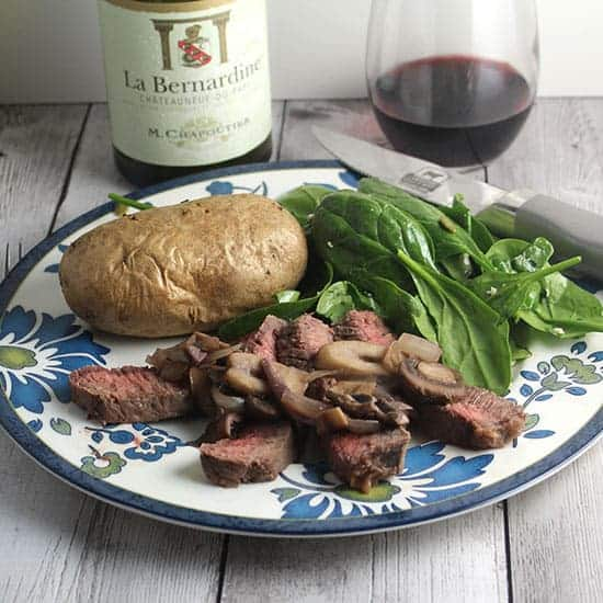London broil steak topped with mushrooms served with potato, salad and red wine.