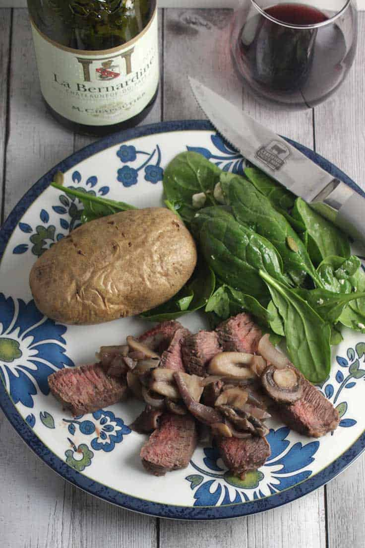 London broil steak top with mushrooms served with potatoes and salad, paired with red wine.