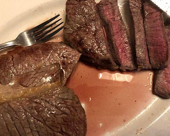 London broil steak sliced on a platter.
