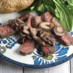 london broil steak topped with mushrooms
