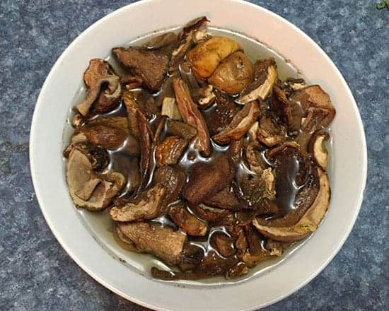 dried porcini mushrooms soaking in a bowl of warm water.
