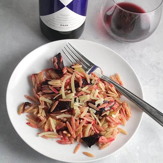 plate of roasted beet orzo served with red wine.