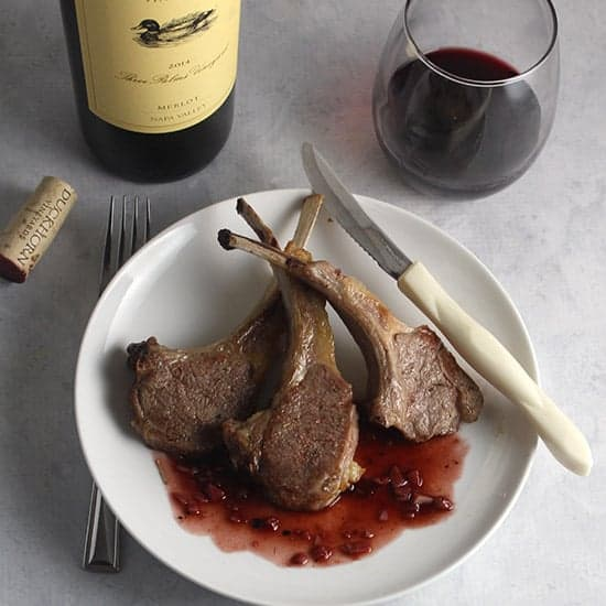 roasted lamb chops on a plate with blackberry sauce, served with a Duckhorn Merlot wine.