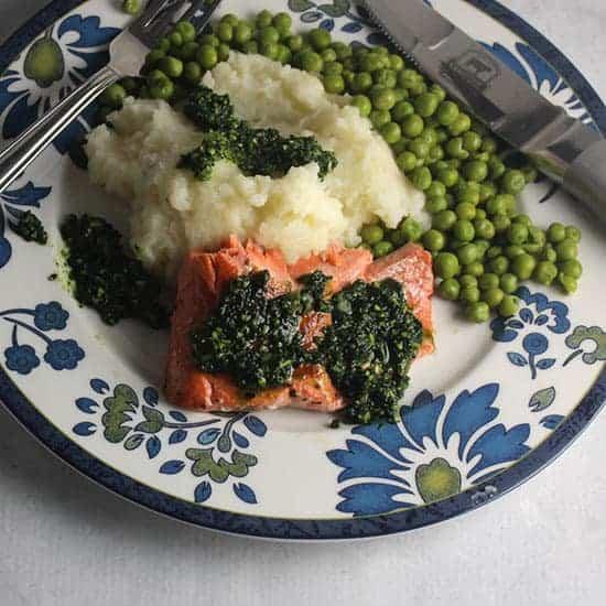 salmon topped with pesto served alongside mashed potatoes.