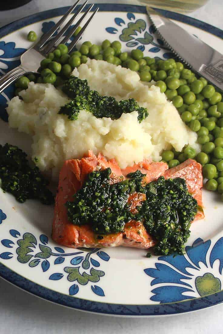 salmon topped with kale pesto on a plate with mashed potatoes and peas.