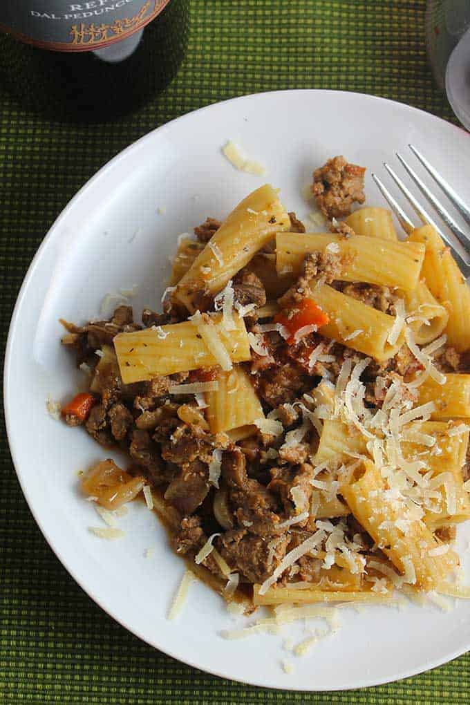 turkey Bolognese pasta with porcini mushrooms on a white plate.