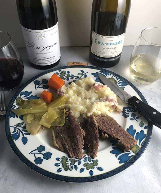 corned beef and cabbage served with a bottle of red and a bottle of white wine.