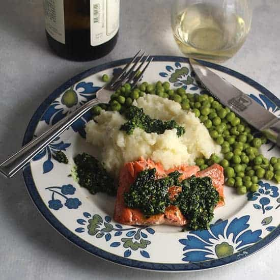 Salmon with Pesto served with potatoes, peas and a glass of white wine.