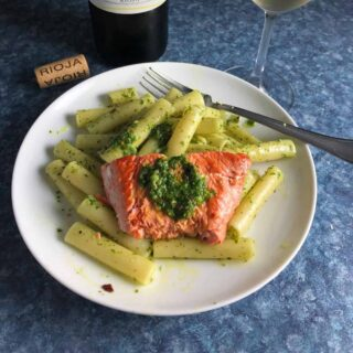 salmon served on a plate with pesto and pasta.