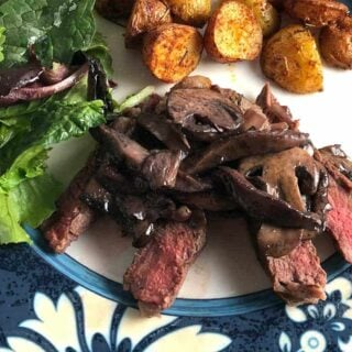 steak topped with Manchego mushroom sauce served with salad and potatoes.