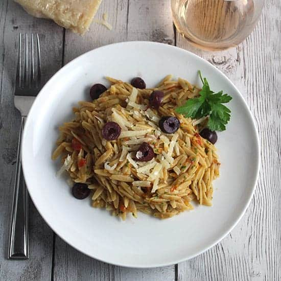 plate with orzo tossed with Provencal Pesto and topped with olives and cheese.