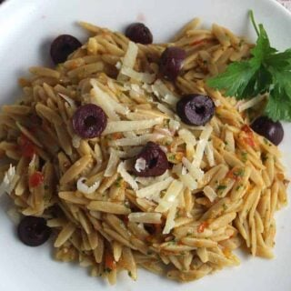 plate with orzo topped with provencal pesto and olives.