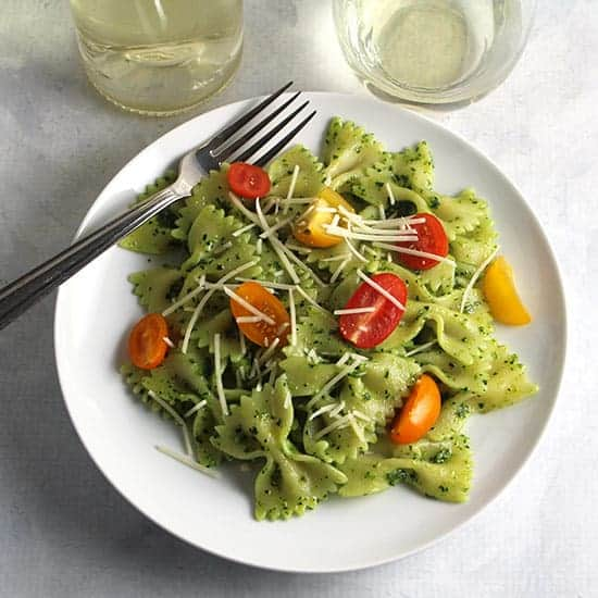 plate with bowtie pasta tossed with pesto, topped with tomatoes.