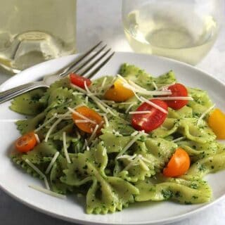 bow tie pasta with pesto and tomatoes on a plate with white wine.