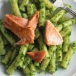 plate with pesto pasta topped with salmon