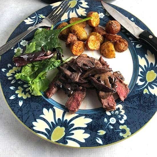 steak with Manchego mushroom sauce on a plate with potatoes and salad.