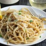 plate with spaghetti tossed with Asiago cheese and lemon.