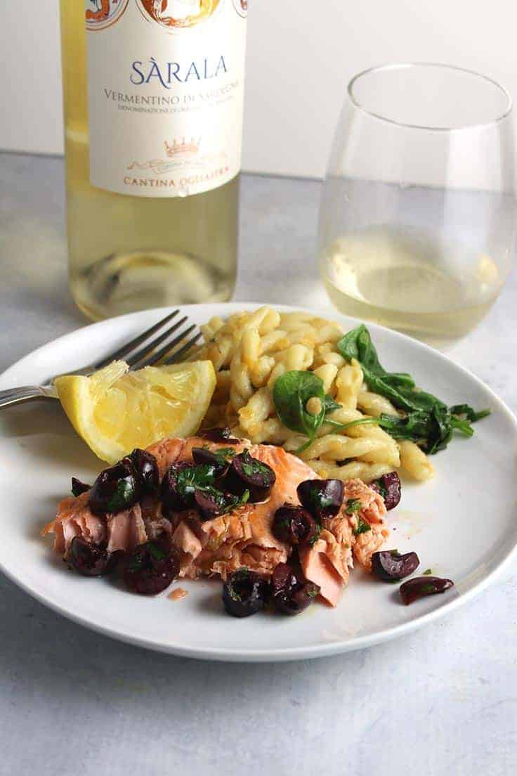 Pan seared salmon topped with lemon olive relish and served with a Vermentino white wine. #salmon #seafood #winepairing #Vermentino