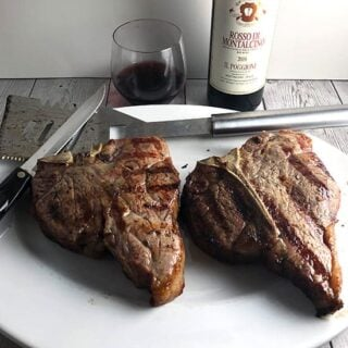 bistecca alla Fiorentina on a platter with red wine in background.
