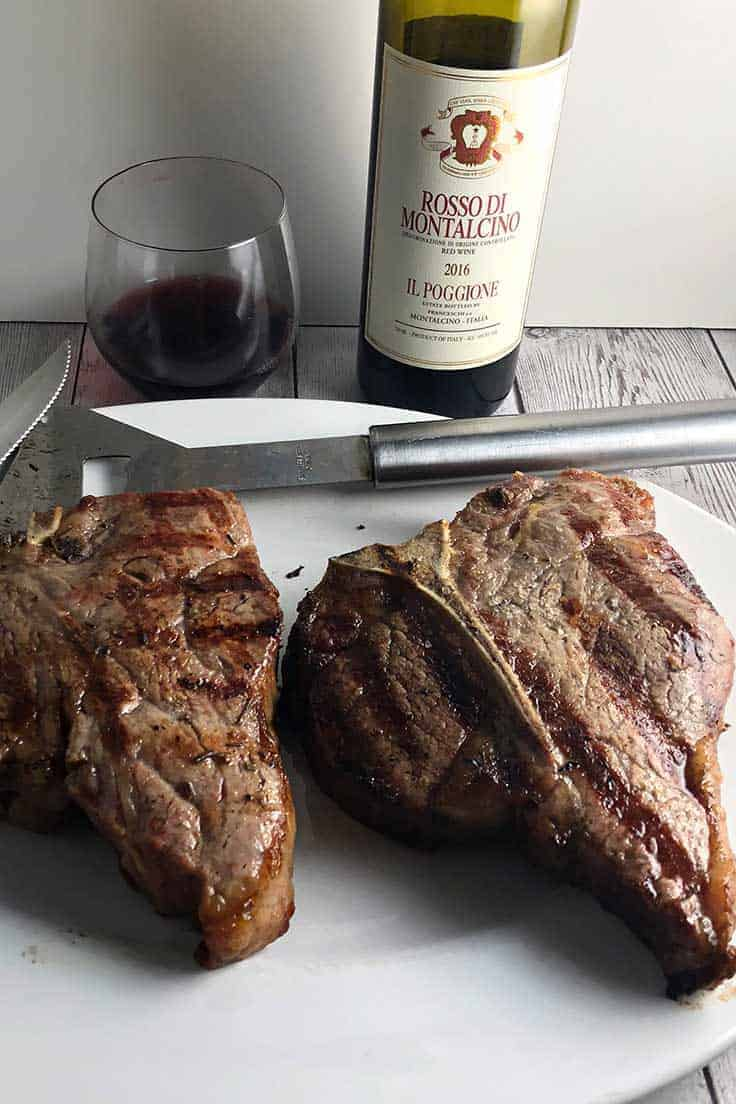 Bistecca alla Fiorentina on a platter with red wine in the background.