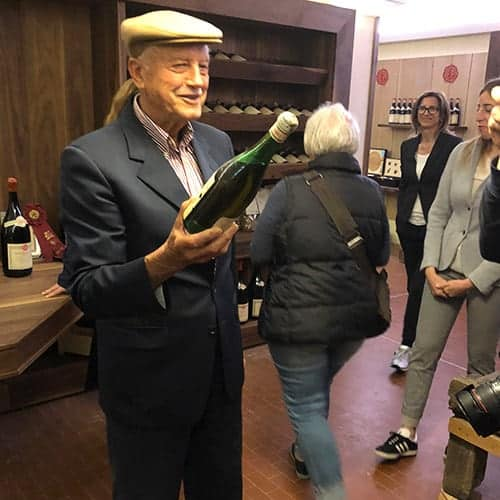 Emidio Pepe showing a bottle of wine to visitors.