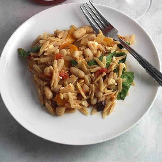 orzo with spinach, beans and vegetables on a plate.