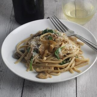 spinach and mushroom pasta served with white wine.
