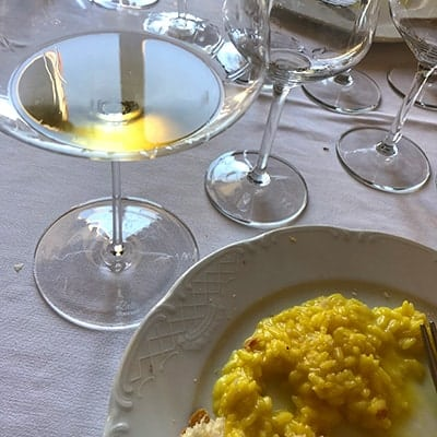 glass of Trebbiano white wine next to saffron risotto.
