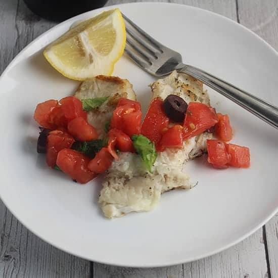grilled tilapia with tomatoes on a white plate.