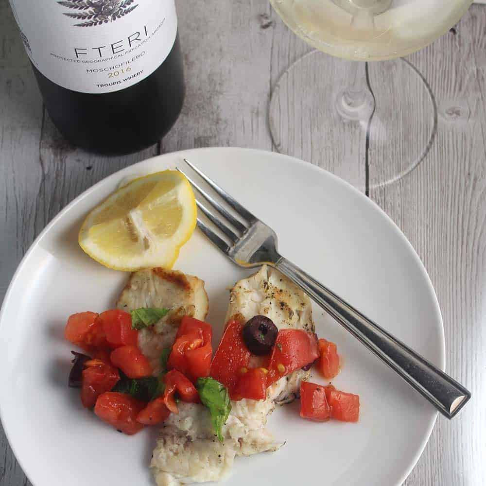 grilled tilapia on a plate with Greek white wine.