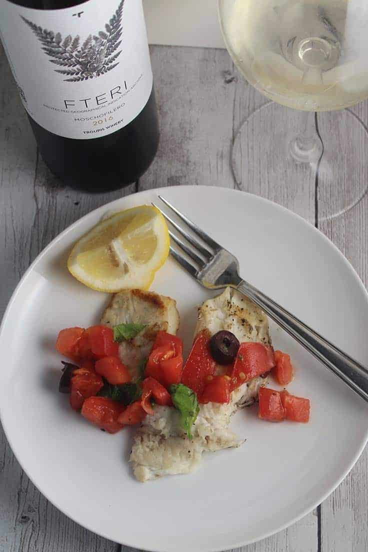 grilled tilapia topped with tomatoes and olives and paired with a Greek white wine. Delicious Greek inspired wine pairing! #grilledfish #winepairing #tilapia