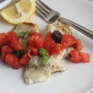 grilled tilapia topped with tomatoes and olives, with a lemon on the side.
