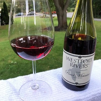 Bottle of Westport Rivers Pinot Meunier red wine, with a glass of it nearby.