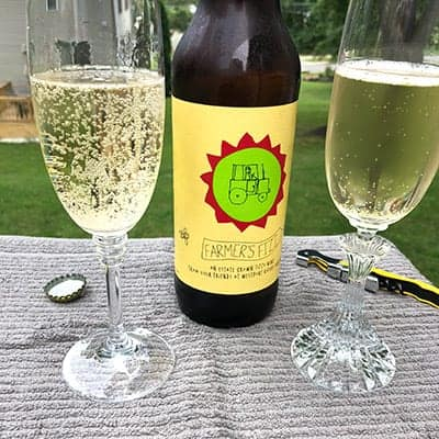 Bottle of Westport Rivers Farmers Fizz and two glasses of the sparkling wine.
