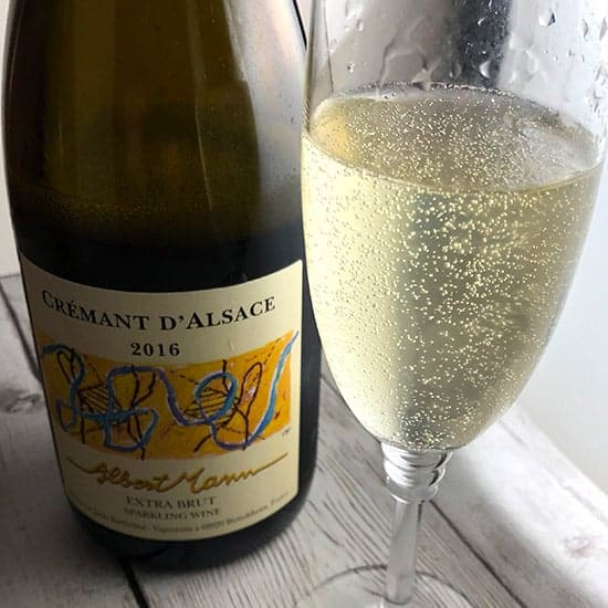 glass of Albert Mann Crémant d'Alsace next to the bottle.