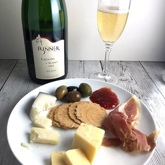 Binner Crémant d'Alsace with cheese, olives and ham on a plate.