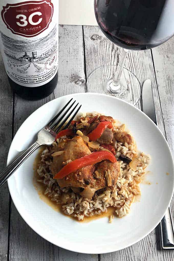 Chicken Chilindron, a delicious Spanish braised chicken thighs recipe with onions and peppers. Served with Cariñena Spanish red wine. #chickenthighs #braising #winepairing #sponsored