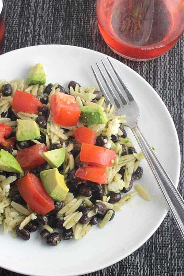 Orzo tossed with zesty cilantro pesto and black beans, topped with tomatoes and avocado. #cilantro #pesto #orzo