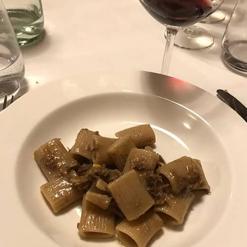 pasta with meat sauce in a white dish, with a glass of red wine.